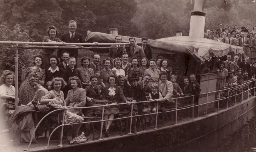 Sepia photo of a large group of people aboard a steam barge